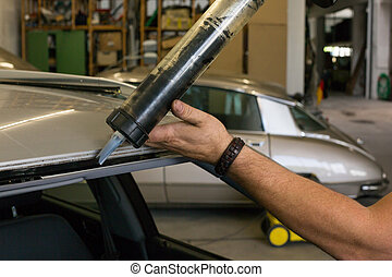 Glazier using application gun to apply adhesive for...