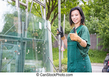 Glaziers loading panes of glass on trailer - Glaziers...