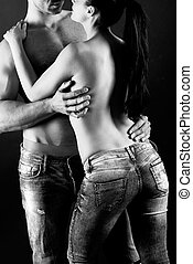 Sexy young couple with blue jeans standing together, studio...
