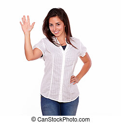 Smiling young woman gesturing a greeting with hand