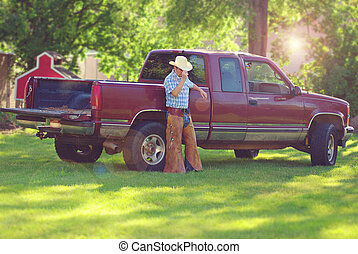 Cowboy - A man leaning against his work truck
