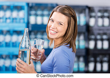 Woman with water - Smiling brunette woman holding water...