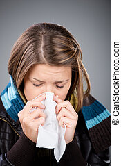 Sneezing woman wearing jacket and scarf in a close up shot