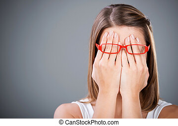 Woman with glasses - Young brunette woman covering face...