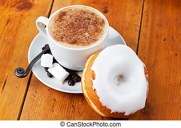 Fresh cappuccino and doughnut with white frosting