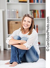Charming young woman sitting on the floor mat