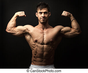 Portrait of muscular man flexing his biceps - Waist-up...