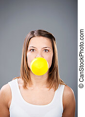 Blowing yellow balloon - Brunette woman blowing yellow...