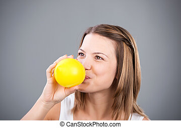 Blowing balloon - Cheerful woman blowing yellow balloon in a...