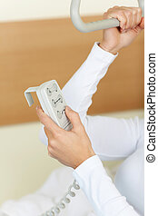 Patient adjusting the bed with a remote controller -...