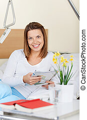 Happy young female patient reading a magazine - happy young...