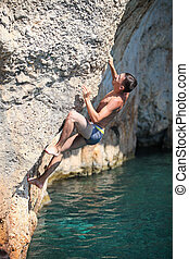 Deep water soloing, rock climber on cliff - Deep water...