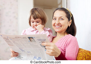 Mature woman and girl reads newspaper - Mature woman and...