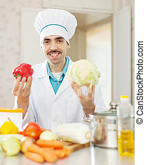 Happy cook man in toque with vegetables