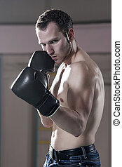 Waist-up of male boxer in gym - Waist-up of young male boxer...