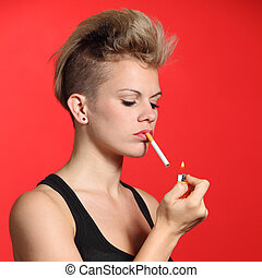 Fashion woman lighting a cigarette with a red background