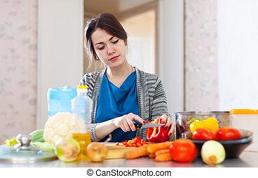 woman cuts red pepper - beautiful woman cuts red pepper