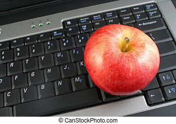 healthy workplace - a business laptop with shiny red apple...