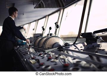 Navigation officer driving ship on the river. - Navigation...