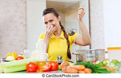 woman holding her nose because of bad smell from food