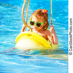 Baby girl swinging on water attractions - Closeup portrait...