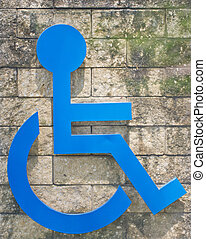 Blue handicapped sign on the rock wall