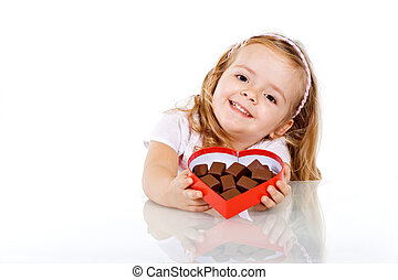 Happy little girl with chocolate in heart shaped box -...
