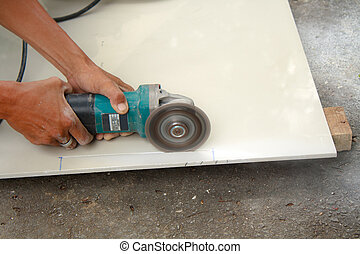 Tile cutter - Workers are using tools for cutting tile.