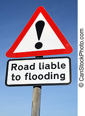 Road liable to flooding warning sign and a blue sky