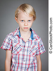 Sad grumpy young boy - Sad cute grumpy young boy looking at...