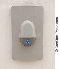 Buzzer - Gray buzzer on a white wall.