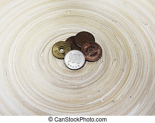 Japanese Hundred Yen Coin and Other Coins on Bamboo Circular...