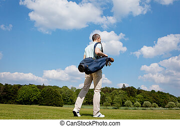 Mature Male Golfer Carrying Bag On Course - Full length rear...