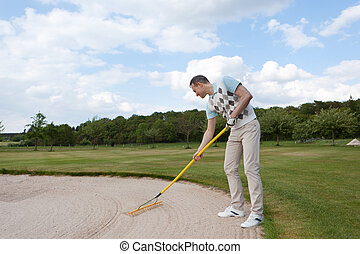 golfer racking sand - full length view of a golfer racking...