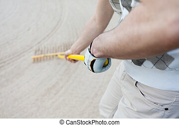 Golfer Racking Sand At Golf Course - Midsection of golfer...