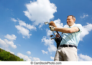 Man Removing Golf Club Against Sky - Low angle view of...