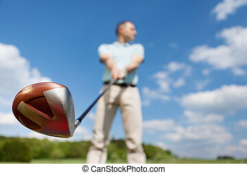 Man Holding Golf Club Against Sky - Low angle view of man...