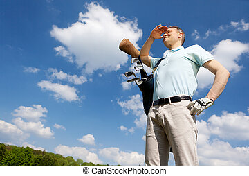 golfer against blue sky - low angle view of a golfer against...