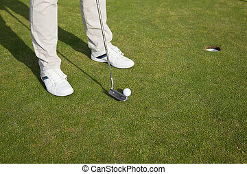 golfer putting ball - golfers feet with ball in front of the...