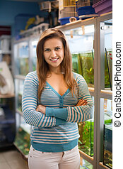 Woman near fish tanks - Woman near aquariums with fishes in...