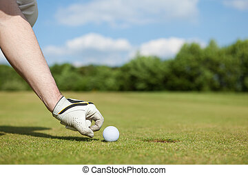 Mans Hand Putting Golf Ball In Hole - Close-up of a mans...