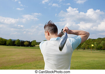 practising golf - rear view of a man practising golf with...