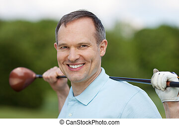 Man Smiling While Holding Golf Club