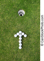 golf balls arranged as arrow sign near the hole
