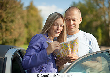 couple looking at the map on  road