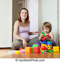 Happy pregnant mother plays with child
