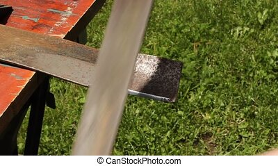 filing a mower blade - using a file to hand sharpen a...