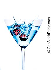 red dice falling in the blue cocktail glass with splashes on...