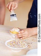 Child decorating a cupcake glazing the top with icing using...