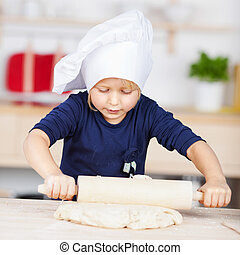 Little girl in a chefs hat rolling pastry - Cute little girl...